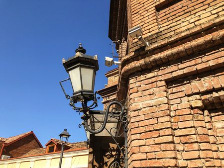 Old Tbilisi architecture. The bricks wall and  street light in summer day.