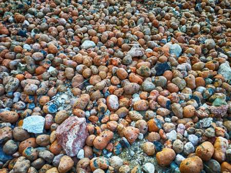 Texture of colored stones. A wall of red gravel. The stones are small and medium. Land is covered.