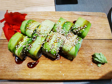 Philadelphia rolled sushi on a wooden sushi board. Vegetarian Japanese seafood
