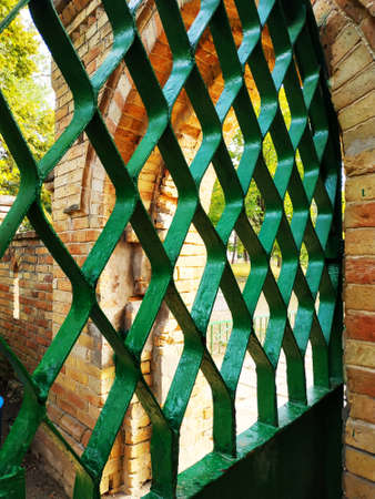 Old painted metal fence. Entrance through the fence.