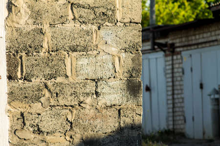 Exterior texture of yellow brick and wall outside. Grunge background. Countryside. Old garage parts.