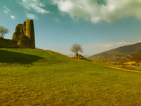 Ruins of an old fortress against the sky, panoramic view. Spring, green fields. Standard-Bild