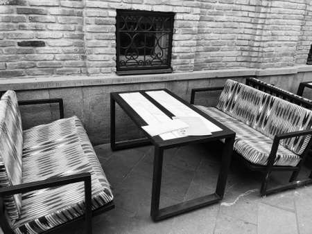 Old Tbilisi architecture, cafe table and chairs in summer day.