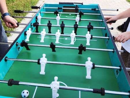Outdoor in summer residence. Kick off strike in table football game.