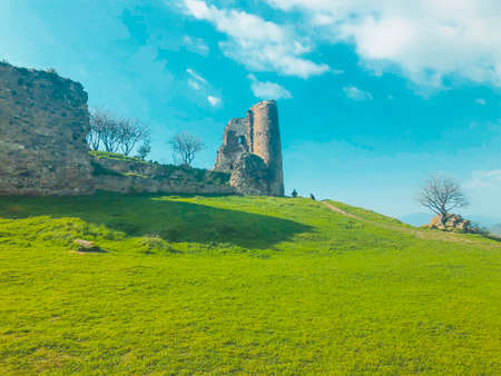 Ruins of an old fortress against the sky, panoramic view. Spring, green fields. Imagens - 150634477