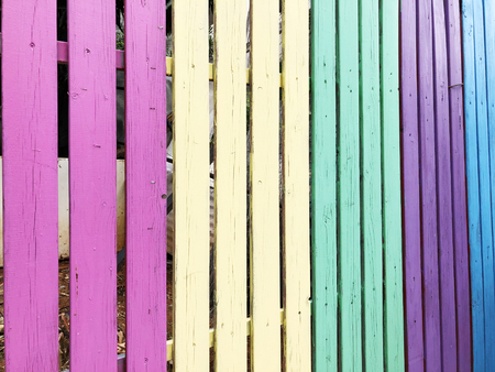 Wooden fence painted in different colors . Close up shot.