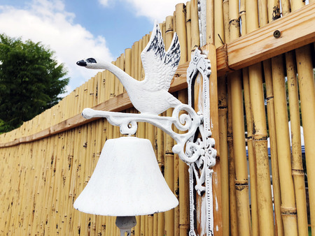 Wooden fence and decorative iron doorbell  . Close up shot. Stok Fotoğraf