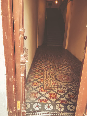 The entrance to the old building. Colored decorative ornament of the floor. Old Tbilisi architecture.
