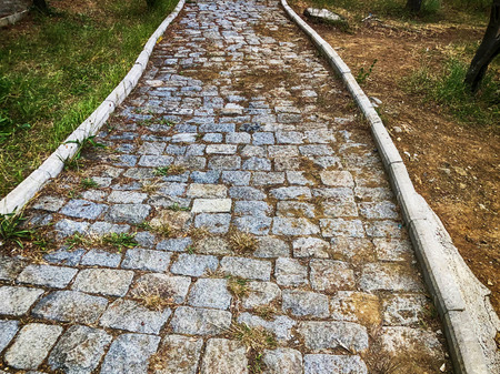 Stone lined footpath, sprouted grass among stones. The road of the Mtatsminda Park on the funicular in Tbilisi. 版權商用圖片
