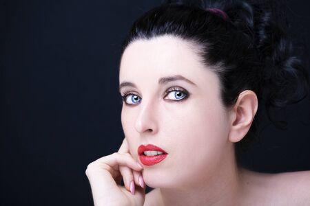 Jonge aantrekkelijke vrouw met lang zwart haar op donkere achtergrond.