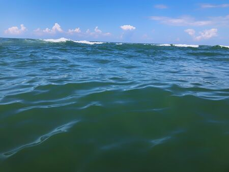 Close up of sea wave. Front view on beautiful sea wave on sandy beach. Summer sunny day, blue sky, water background.