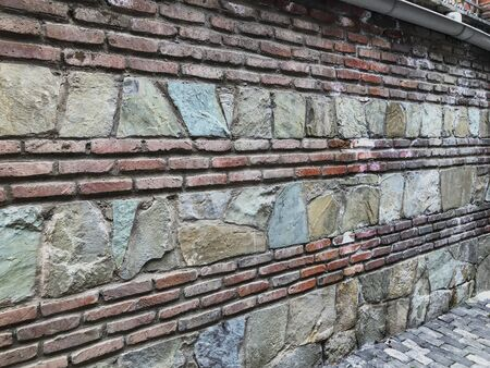 Renovaited red brick and stone old wall. Colored brick wall. Urban texture. Texture brick ans stone wall background.