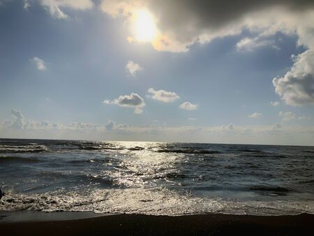 View of the sea, sky and clouds during sunset. Glitter waves on a sandy beach. Summer sunny day, water background.