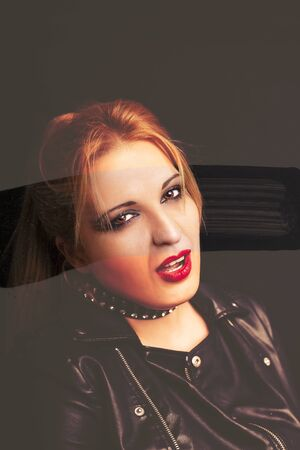 Beautiful blonde girl in rock style on a black background
