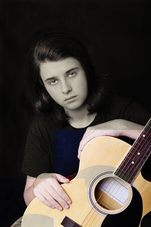 Portrait of a teenager playing guitar in studio