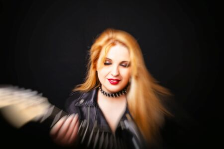 Beautiful blonde girl in rock style on a black background. Blur motion effect Stock Photo
