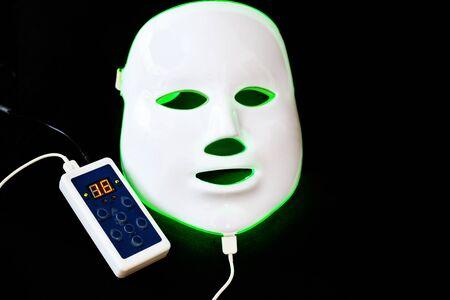 Light rejuvenating mask for facial skin therapy on black background 写真素材