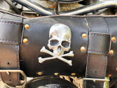 Leather biker bag with skull and bones on a motorcycle close-up. Concept travel on a motorcycle.