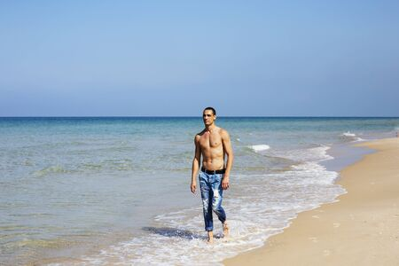 young muscular man resting and posing on the beach. A young man walks by the sea.