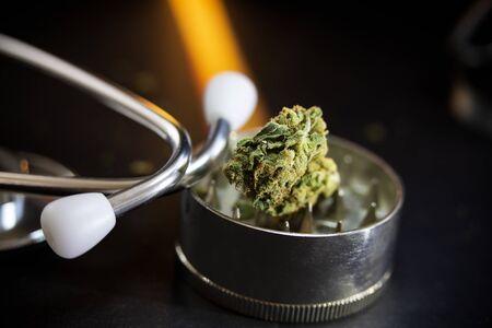 Marijuana and metal grinder with marijuana isolated on a black background. Фото со стока - 133477123