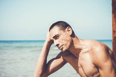 young muscular man resting and posing on the beach. 写真素材