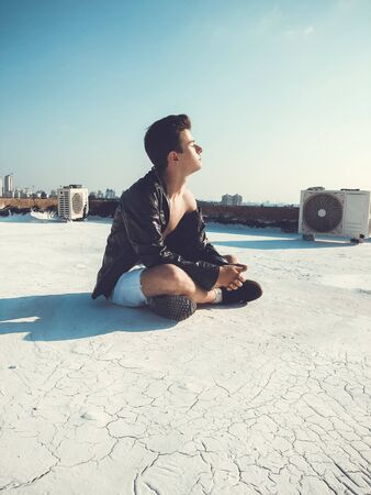 Young attractive man posing in front of camera on the roof of a residential building. 写真素材