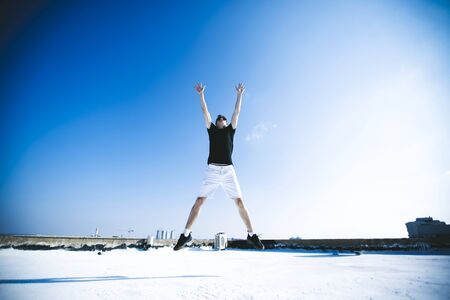 Young attractive man jumping in the air on the roof of a residential building. 写真素材 - 134794004