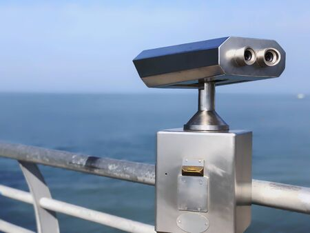 Paid outdoor tourist telescope made of stainless steel on the sea coast over blue sky background.