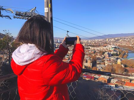 Girl in a red jacket taking pictures of the city. Beautiful landscape view of the old district with modern area. Old Tbilisi, winter in the city. 写真素材