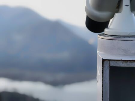 Paid outdoor tourist telescope made of stainless steel on the against the backdrop of extending mountains and a river.