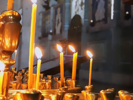 Burning candles on the background of icons in the church. 写真素材