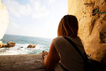ROSH HANIKRA, ISRAEL - 6 SEPTEMBER, 2017:A young woman looks out over the sea Rosh Hanikra, Israel.