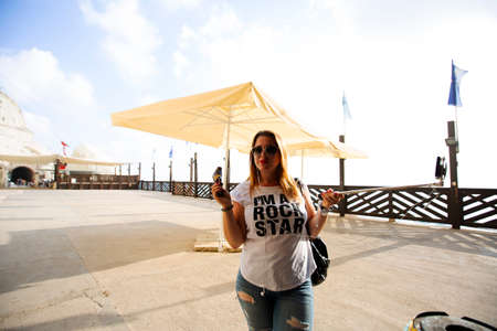 ROSH HANIKRA, ISRAEL - 6 SEPTEMBER, 2017: A young woman poses with a selfie stick Rosh Hanikra, Israel.