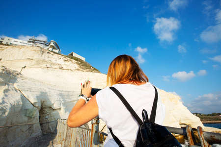 A young woman takes a photo with a mobile phone rosh hanikra, Israel. Imagens