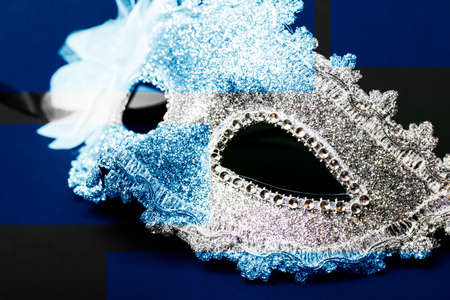 White human carnival mask isolated on dark background. Close-up