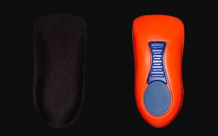 The orthopedic insole on a black background. Treatment and prevention of flat feet and foot diseases. High quality photo