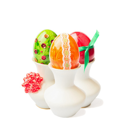 three colored easter eggs in cup with ribbon on white background photo