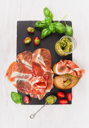 prosciutto ham with bread, basil pesto and tomatoes on slate and white wooden background, top view Stock Photo