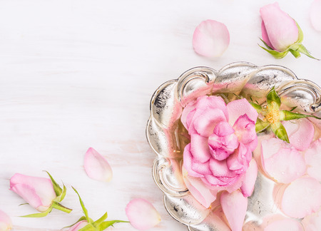 Silver bowl with roses and water on white wooden background Imagens