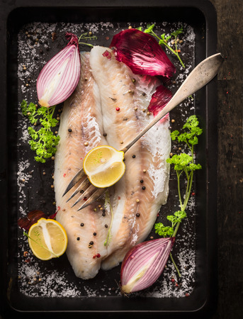zander: raw fish with herb, spices and fork on black old backing tray, top view Stock Photo