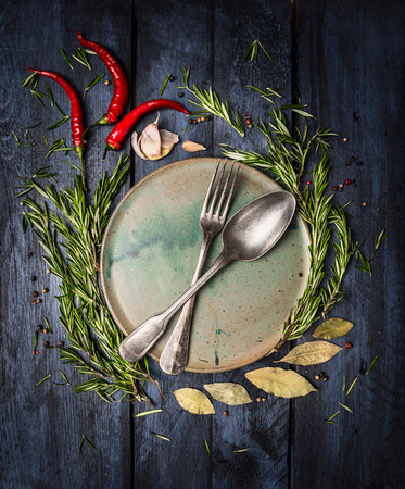 Spoon and Fork on plate with herbs and spices frame on dark blue wooden table, top view