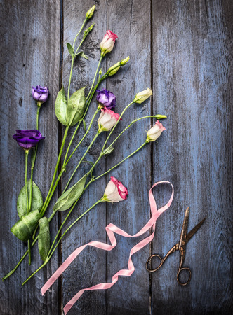 romantic flowers: summer flowers with ribbon and  scissors on blue wooden table, top view Stock Photo