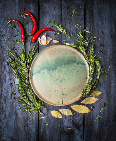 spices: Herbs and spices around platte on dark blue wooden background, top view, place for text