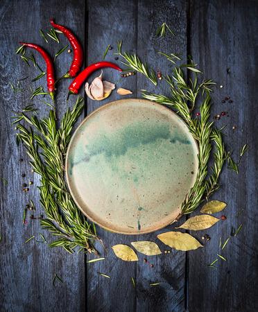 ESPECIAS: Hierbas y especias alrededor de Platte sobre fondo azul oscuro de madera, vista desde arriba, el lugar de texto