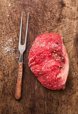 dark meat: Raw meat Striploin steak with fork, salt and pepper on old wooden background, top view Stock Photo