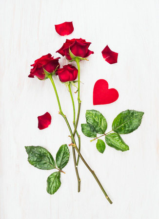 long stem: three red roses on long stems and heart on white wood, love card