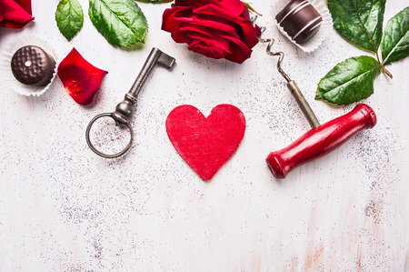 love rose: heart, red rose, chocolate , key and corkscrew on white wooden, love background, top view, place for text