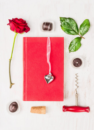composing: Love story composing with book, heart, red rose, chocolate and corkscrew on white background, top view Stock Photo