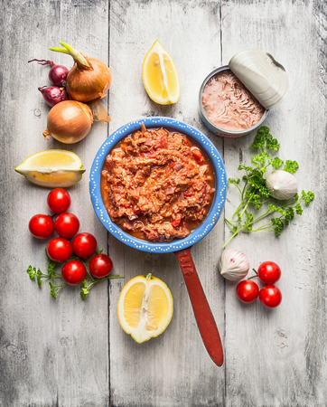 canned food: Tomato sauce with canned tuna in rustic pot with vegetables and spices, white wooden background, top view