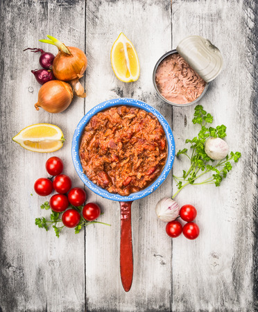 tomato sauce with tuna fish in old porridge pot and ingredient on white wooden background, top view photo